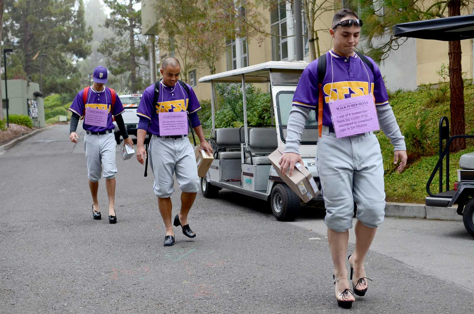 Jack Veronin (left), Peter Reyes (middle) and Carter Loud (right), members of the SF State baseball team, walk in heels for The SAFE Place and Men Can Stop Violence event titled: Walk in Her Heels. This event is a men's walk to stop rape, sexual assault, and gender violence. Men volunteers sign up, pick up heels and go about their normal days wearing these shoes and collecting donations with a shoe box until noon where the men come together in Malcolm X Plaza at SF State on Tuesday, October 22 to share their experience, if they so choose. Photo by Virginia Tieman / Xpress