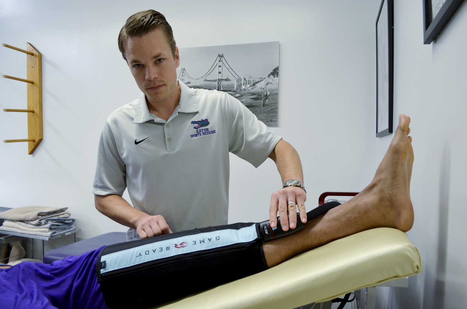 Bryce Schussel, the head athletic trainer at SF State since June 2009, works with SF State men's basketball player Eric Fearn in the training room in the Gymnasium building Friday, Nov. 15, 2013. Photo by Amanda Peterson / Xpress