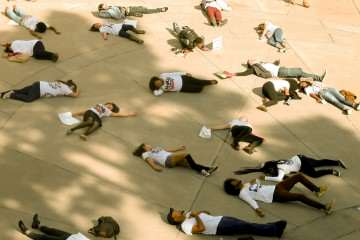 SF State students fall to the ground at the Die In in memory of all of the innocent lives lost through police hands. The attendants came together to march in a national day of protest to stop police brutality, repression and the criminalization of a generation Wednesday, Oct. 22, 2014 at Malcolm X Plaza. Amanda Peterson / Xpress.