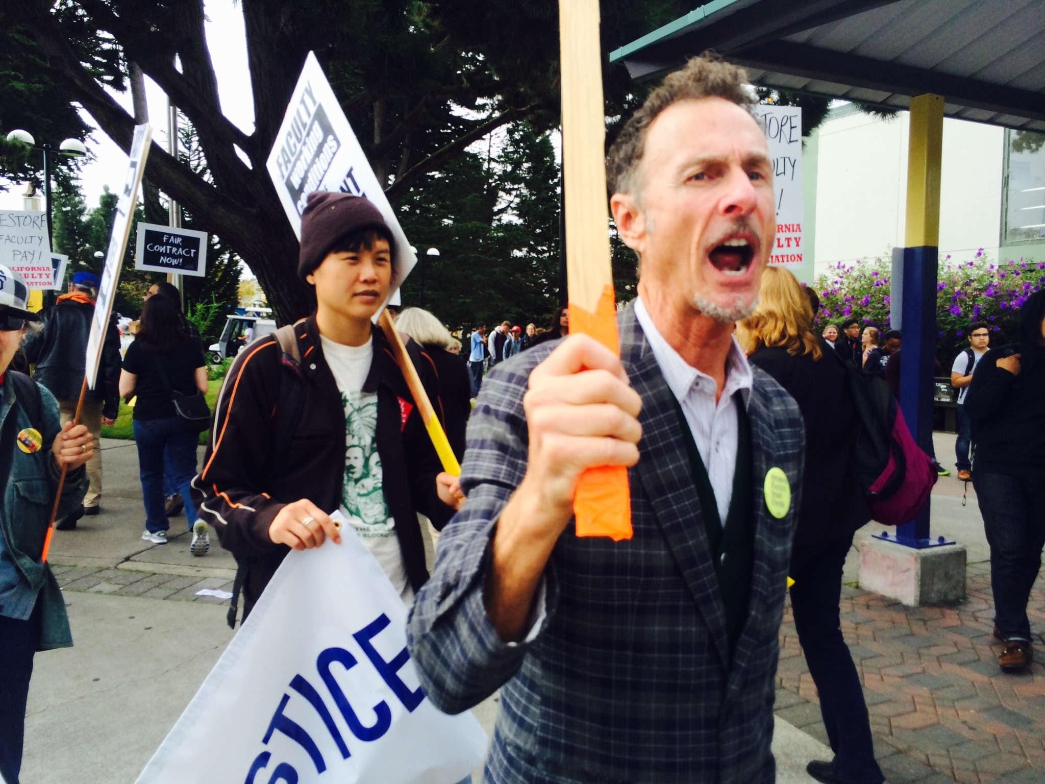 Michael Ritter marches and chants in a picket line in front of SF State Tuesday, Oct. 7, 2014. Students and faculty members gathered at the corner of 19th and Holloway avenues occupying part of the campus entrance.