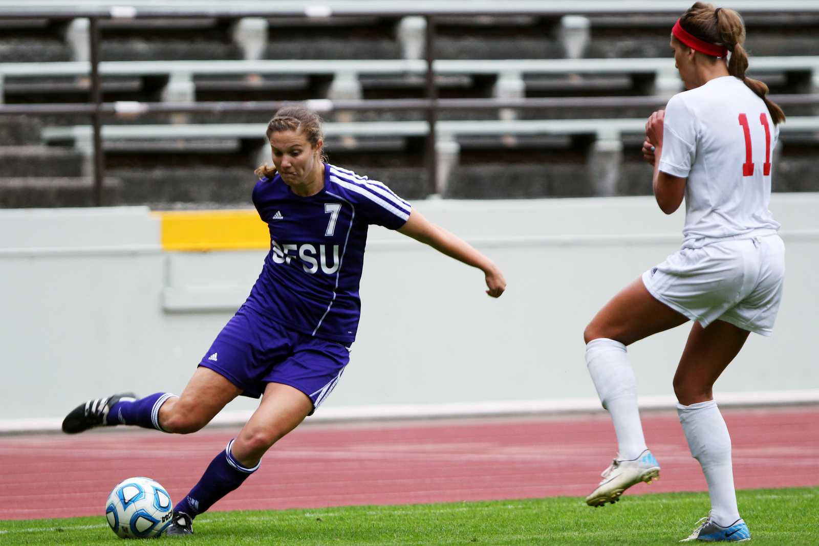 Mari Mendizabal (7) kicks the ball past Rachel Crawford(11) during a game featuring the SF State Gators vs the Western Oregon University Wolves at Cox Stadium on September 11, 2013. The Gators tied the Wolves in the second half of the game, the final score was 1-1. Photo by Gavin McIntyre / Xpress