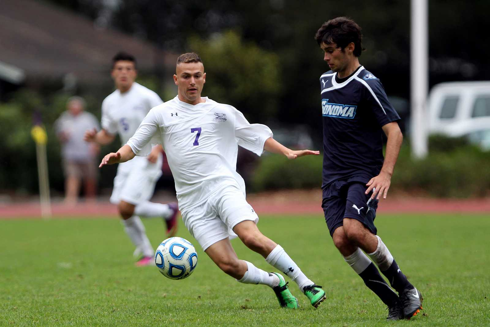 Cole Dimond (7) (left) kicks the ball past Sean Callahan(8) during a game between the SF State Gators and the Sonoma State University Seawolves at Cox Stadium on Sept.13, 2013. The Gators lost in a hard fought battle against the Seawolves, losing 0-1. Photo by Gavin McIntyre / Xpress