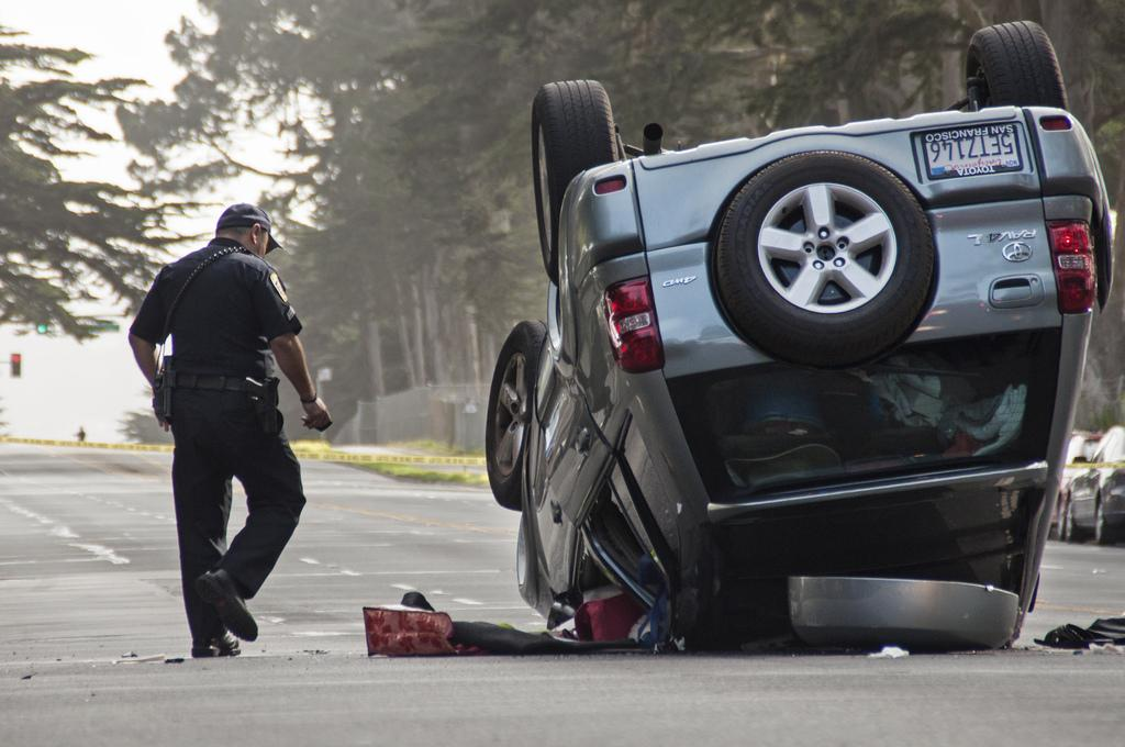 A police officer investigates the scene after a driver blacked out and flipped their car on Lake Merced Boulevard between Font Boulevard and Higuera Street around 2:30 p.m. Thursday, March 6. Photo by Jessica Christian / Xpress